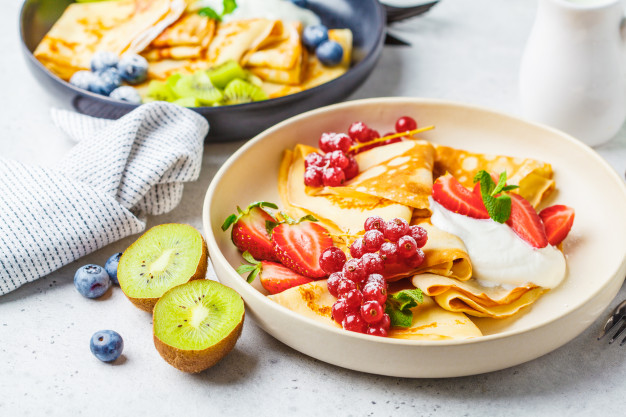 homemade-thin-crepes-served-with-curd-cream-fruits-berries-black-white-plates_79830-93