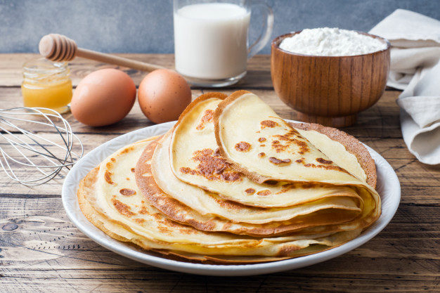 thin-pancakes-plate-wooden-background-ingredients-cooking-eggs-milk-flour_78677-179