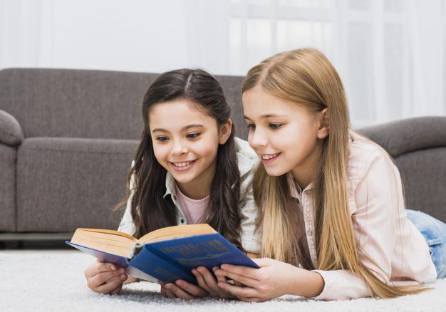 two-pretty-girls-lying-carpet-reading-book-together-home_23-2148080329